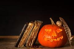 万圣夜南瓜和咒语书  被雕刻的南瓜 登记魔术 传统的节假日 库存图片