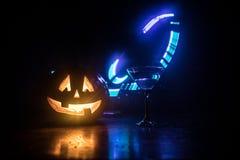 万圣夜南瓜桔子鸡尾酒 欢乐的饮料 万圣节当事人 与一个发光的鸡尾酒杯的滑稽的南瓜在黑暗定了调子fo 皇族释放例证