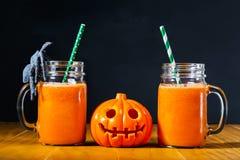 万圣夜南瓜用在金属螺盖玻璃瓶的红萝卜汁 免版税图库摄影