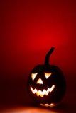 万圣夜南瓜,在红色背景的滑稽的面孔 免版税库存图片