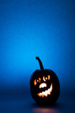 万圣夜南瓜,滑稽的面孔剪影在蓝色背景的 免版税图库摄影