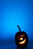 万圣夜南瓜,滑稽的面孔剪影在蓝色背景的 免版税库存照片