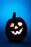 万圣夜南瓜,滑稽的面孔剪影在蓝色背景的 免版税库存图片