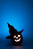 万圣夜南瓜,滑稽的面孔剪影在蓝色背景的 库存图片