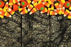 万圣夜反对木头和黑布料背景的糖果边界 免版税库存照片