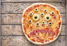 万圣夜可怕食物妖怪蛇神面孔薄饼快餐用无盐干酪和香肠 图库摄影