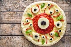 万圣夜可怕食物滑稽的眼睛妖怪薄饼margherita用无盐干酪 图库摄影