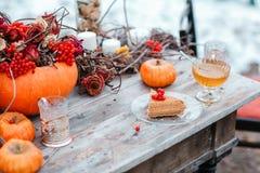 万圣夜启发 仍然秋天生活 南瓜,干燥玫瑰,荚莲属的植物蜜糕 在花瓶 枝杈 在桌上 免版税库存图片