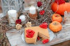 万圣夜启发 仍然秋天生活 南瓜,干燥玫瑰,荚莲属的植物蜜糕 在花瓶 枝杈 在桌上 免版税图库摄影