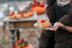 万圣夜启发 蛋糕在手上 仍然秋天生活 南瓜,干燥玫瑰,荚莲属的植物蜂蜜 在花瓶 枝杈 在 库存照片