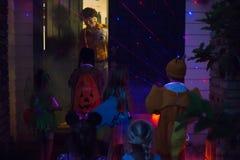 万圣夜和孩子把戏或款待去挨门挨户在晚上 库存图片