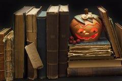 万圣夜和老巫婆书的南瓜灯笼 从一个南瓜雕刻的头在万圣夜 南瓜传统 免版税库存图片