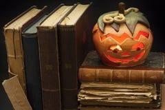 万圣夜和老巫婆书的南瓜灯笼 从一个南瓜雕刻的头在万圣夜 南瓜传统 免版税库存照片