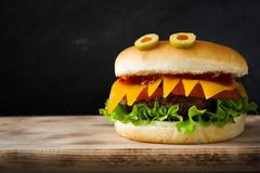 万圣夜在木桌上的汉堡妖怪 免版税库存图片