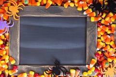 万圣夜在粉笔板附近的糖果框架 免版税库存图片