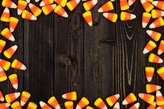万圣夜在黑暗的木头的糖味玉米框架 免版税库存图片