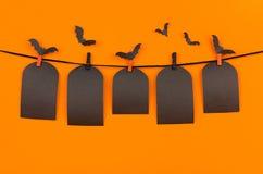 万圣夜垂悬在晒衣夹的群棒和黑空白的标签坟茔,在橙色背景,嘲笑  库存照片