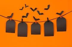 万圣夜垂悬在晒衣夹的群棒和黑空白的标签坟茔,在橙色背景,嘲笑  图库摄影