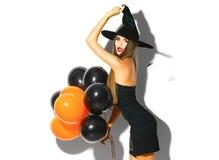 万圣夜女招待 拿着黑和橙色气球的性感的巫婆 库存图片