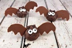 万圣夜巧克力多福饼孔击反对白色木头 库存图片