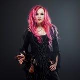 万圣夜巫婆创造魔术 有红色头发的可爱的妇女在伏都教巫婆服装 免版税图库摄影
