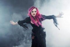 万圣夜巫婆创造魔术 有红色头发的可爱的妇女在巫婆打扮身分被伸出的胳膊,强风 免版税库存图片