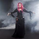 万圣夜巫婆创造魔术 有红色头发的可爱的妇女在巫婆服装 免版税库存图片