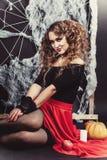 万圣夜巫婆女孩坐与黑墙壁的地板和在背景上的蜘蛛网 投入她的手对膝盖 免版税图库摄影