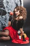 万圣夜巫婆女孩坐与黑墙壁的地板和在背景上的蜘蛛网 拿着石榴 库存图片