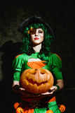 万圣夜巫婆拿着橙色南瓜 库存照片