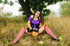 万圣夜巫婆服装的少妇在秋天森林里用黄色南瓜 免版税库存照片