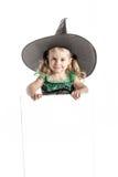 万圣夜巫婆服装的漂亮的孩子有拿着广告的帽子的一个空的委员会 免版税图库摄影