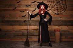 万圣夜巫婆概念-举行摆在与在老木演播室b的不可思议的帚柄的全长愉快的万圣夜红色头发巫婆 图库摄影