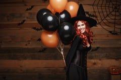 万圣夜巫婆概念-巫婆的美丽的白种人妇女打扮庆祝摆在与摆在的万圣夜用桔子和bla 免版税库存图片