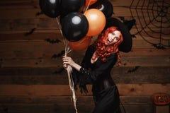 万圣夜巫婆概念-巫婆的美丽的白种人妇女打扮庆祝摆在与摆在的万圣夜用桔子和bla 免版税库存照片