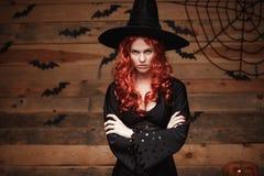 万圣夜巫婆概念-握胳膊的万圣夜红色头发巫婆摆在与在老木演播室背景的恼怒的面孔 库存图片