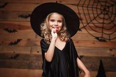 万圣夜巫婆概念-有万圣夜甜点和糖果的小巫婆孩子与快乐微笑 在棒和蜘蛛网backgro 库存图片