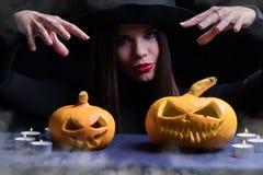 万圣夜巫婆用一个不可思议的南瓜 巫婆的帽子美丽的少妇和服装藏品雕刻了南瓜 万圣夜艺术desig 免版税库存照片