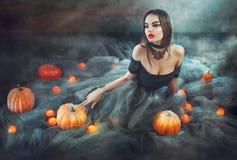 万圣夜巫婆用南瓜和魔术光 免版税库存图片
