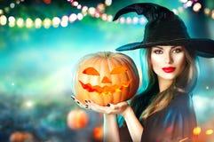 万圣夜巫婆用被雕刻的南瓜和魔术在森林里点燃 免版税库存照片