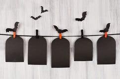 万圣夜广告嘲笑 空白的黑销售标记垂悬在晒衣夹、群棒和白色木板条背景的坟茔 库存图片