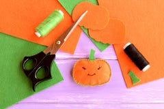 万圣夜微型南瓜装饰品 桔子感觉南瓜、剪刀、毛毡平的片断,绿色和黑色穿线,针 库存图片