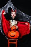 万圣夜恶魔服装的一个年轻男孩用获得的南瓜乐趣 免版税库存照片