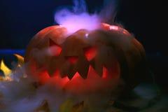 万圣夜有干燥叶子的南瓜灯笼有灼烧的眼睛的 图库摄影