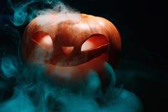 万圣夜有干燥叶子的南瓜灯笼有灼烧的眼睛的 免版税图库摄影