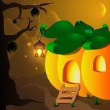 万圣夜有灯的南瓜房子和棒在树 免版税库存照片