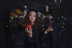 万圣夜服装和装饰的逗人喜爱的矮小的巫婆儿童女孩 免版税库存照片
