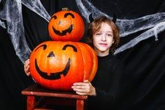 万圣夜服装的一个年轻男孩用获得的南瓜乐趣 库存照片