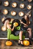 万圣夜服装的两名妇女在党坐在电灯泡背景的椅子 免版税库存照片