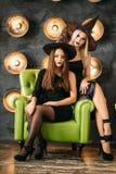 万圣夜服装的两名妇女在党坐在电灯泡背景的椅子 免版税图库摄影